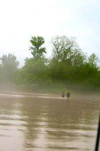 Couple walking into the Mist through the flood waters on Hwy. 50