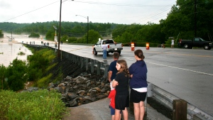 A cluster of people observing flooded bridge