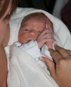 Newborn BabyGirl with her long fingered hands clasped by her face