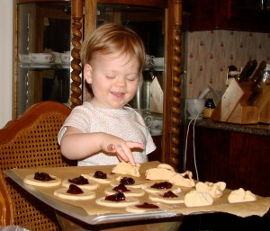 Doodlebug helping to pinch traditional Czech homemade cookies with jam for Christmas treats